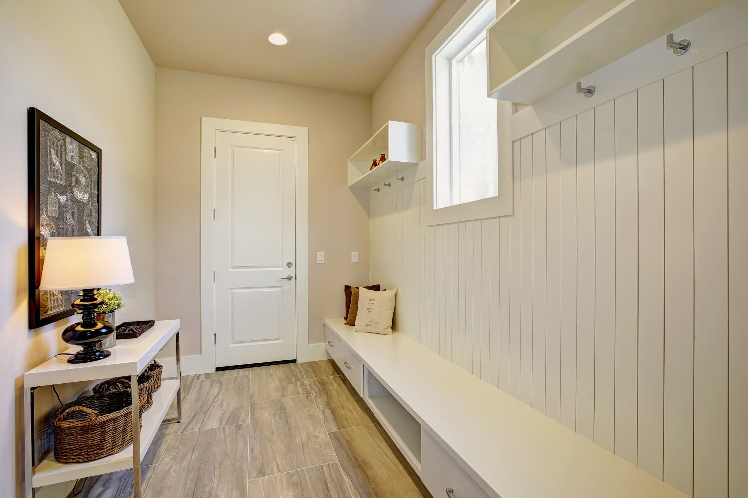 Pretty entrance foyer with a wall clad in diy board and batten siding lined with an extra long built-in bench with storage drawers facing white console table with three round wicker baskets